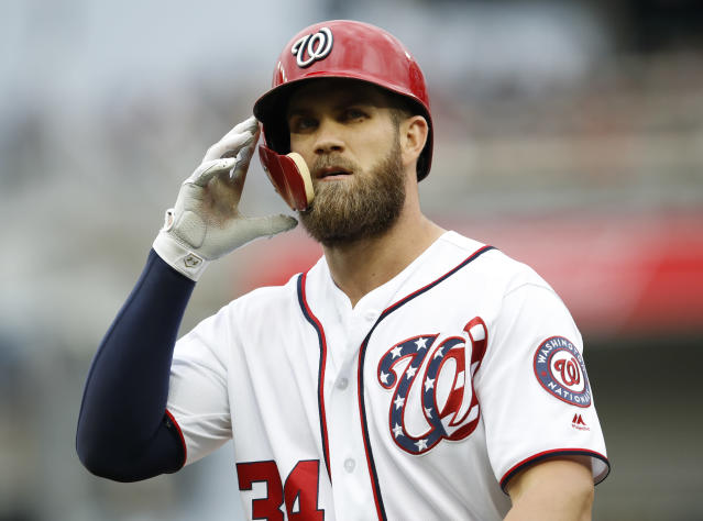 "FILE - In this May 5, 2018, file photo, Washington Nationals' Bryce Harper walks off the field after grounding out during the fifth inning of a baseball game against the Philadelphia Phillies at Nationals Park in Washington. Tune into any game these days and you're bound to see hitters wearing helmets with a seven-inch piece of plastic _ the C-Flap _ curving around their cheek and jaw. ""Just to be, maybe, a little bit more comfortable in the box,"" Harper said. ""Guys are throwing a little bit harder and you see guys getting hit in the head a little bit more. Just trying to be precautionary. Rather have it there if I get hit than not."" (AP Photo/Carolyn Kaster, File)"