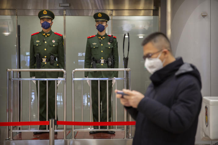 FILE - In this Thursday, Jan. 23, 2020, file photo, Chinese paramilitary police wear face masks as they stand guard at Beijing Capital International Airport in Beijing. British Airways and Asian budget carriers Lion Air and Seoul Air are suspending all flights to China as fears spread about the outbreak of a new virus that has killed more than 130 people. British Airways said Wednesday it is immediately suspending all flights to and from mainland China after the U.K. government warned against unnecessary travel to the country. (AP Photo/Mark Schiefelbein, File)