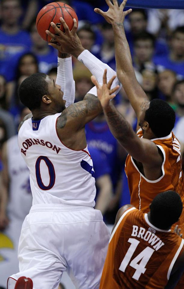 Kansas' Thomas Robinson (0) shoots past Texas' Jaylen Bond, back right, and J'Covan Brown (14) in the second half of an NCAA college basketball game Saturday, March 3, 2012, in Lawrence, Kan. Robinson scored 25 in a 73-63 win.