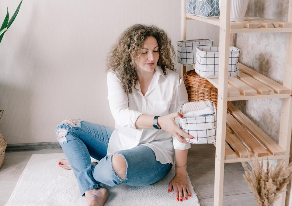 Portrait of a young woman in casual clothes beautifully putting things in containers and boxes. Storage ideas