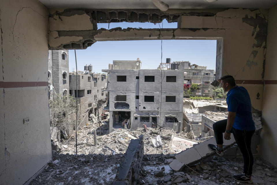 Neighbors walk through a severely damaged home after a neighboring building was destroyed by an airstrike in Magazzi, the Gaza Strip. (John Minchillo/AP)