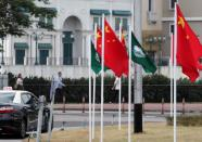 Flags of China and Macau are set up at a traffic ring island in Macau