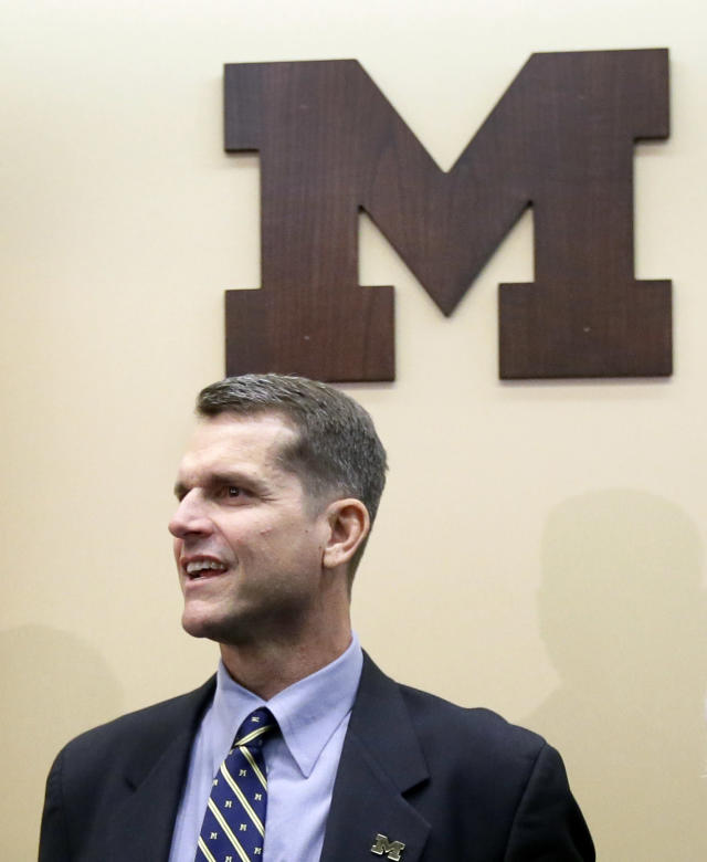 Jim Harbaugh, Michigan's new head football coach, waits after after he was introduced during an NCAA college football news conference, Tuesday, Dec. 30, 2014, in Ann Arbor, Mich. (AP Photo/Carlos Osorio)