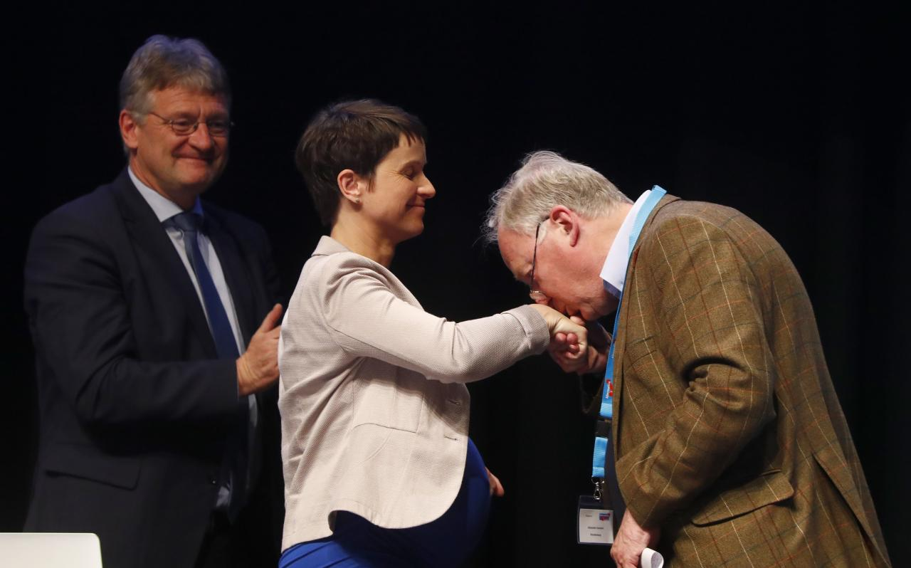 Alexander Gauland of Germany's anti-immigration party Alternative for Germany (AFD) kisses the hand of party chairwoman Frauke Petry as Joerg Meuthen looks on during an AFD party congress in Cologne Germany, April 23, 2017. REUTERS/Wolfgang Rattay  TPX IMAGES OF THE DAY