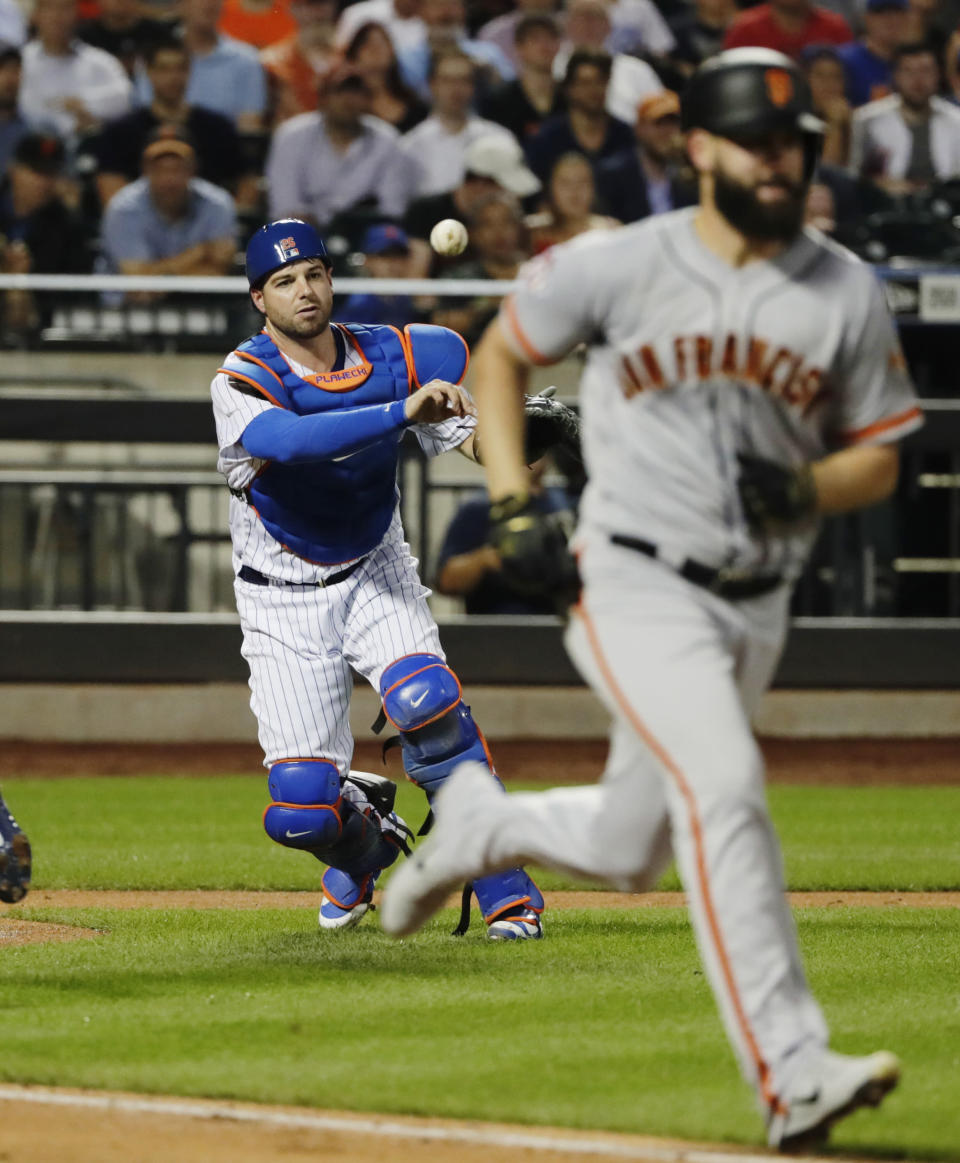New York Mets catcher Kevin Plawecki, left, throws out San Francisco Giants' Casey Kelly on a sacrifice bunt during the third inning of a baseball game Wednesday, Aug. 22, 2018, in New York. (AP Photo/Frank Franklin II)