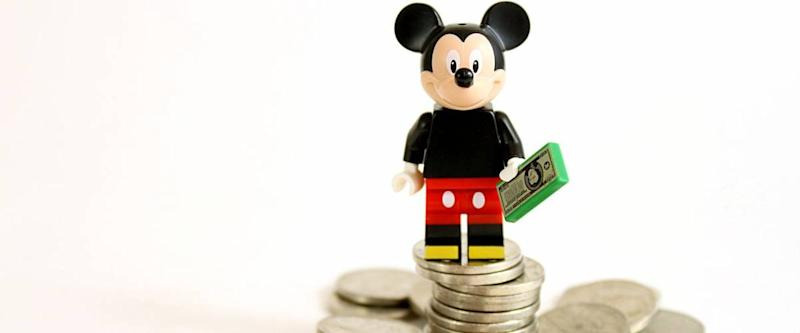 Colorado, USA - May 13, 2016: Studio shot of LEGO minifigure Mickey Mouse on top of a pile of money isolated on white background.