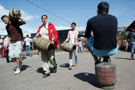 People carry gas cylinders at a distribution point San Cristobal, Venezuela August 3, 2017. Picture taken August 3, 2017. REUTERS/Luis Parada