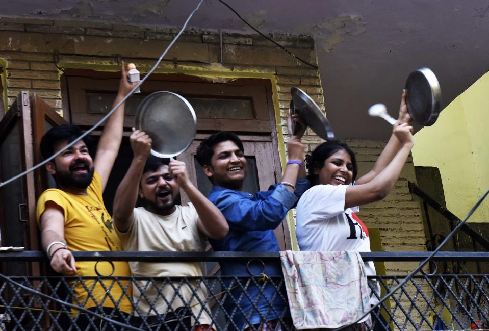 NEW DELHI, INDIA - MARCH 22: People throng to their balconies and streets in a show of appreciation for those engaged in providing essential services to tackle the coronavirus, at Arjun Nagar, on March 22, 2020 in New Delhi, India. A country stalked by an eerie silence came alive, suddenly, at 5pm. Sounds of clapping and beating utensils rang out of residential areas, houses and high-rises, lifting the sombre Sunday mood. Responding to Prime Minister Narendra Modis appeals, citizens across the country came out of their homes and in their balconies, clapping, beating utensils and even ringing bells as a mark of solidarity with health officials and emergency workers who are working tirelessly in the wake of the Covid-19 outbreak. (Photo by Mohd Zakir/Hindustan Times via Getty Images)