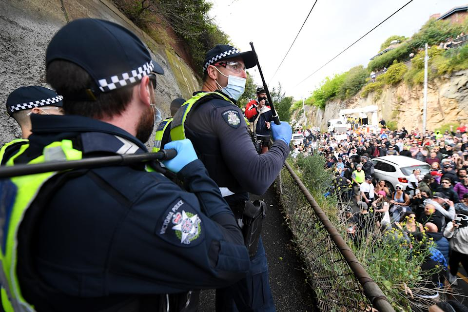 Police watch protesters on the road below at Richmond.