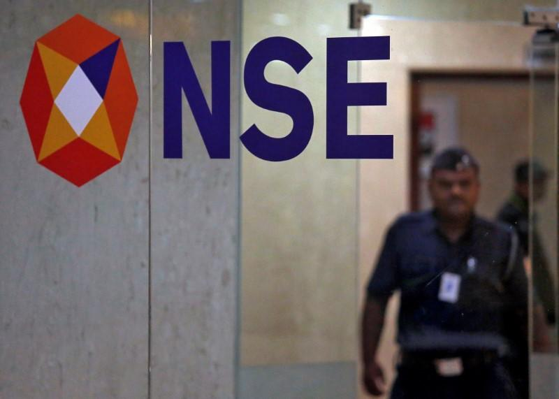 A security guard walks past the logo of the National Stock Exchange inside its building in Mumbai