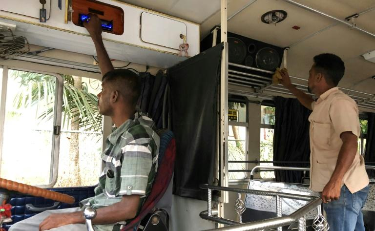 A driver and his assistant check and clean their sound system at the start of a journey in Biyagama, Sri Lanka. The government wants operators to turn down the volume on the notoriously loud vehicles