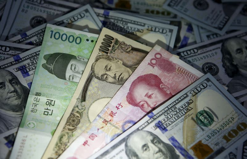 FILE PHOTO: South Korean won, Chinese yuan and Japanese yen notes are seen on U.S. 100 dollar notes in this picture illustration taken in Seoul