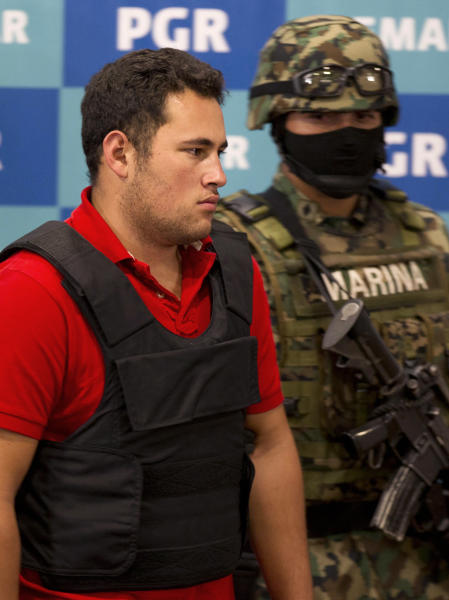 "A Mexican marine escorts Jesus Alfredo Guzman Salazar, left, during his presentation to the media in Mexico City, Thursday, June 21, 2012. Mexican marines detained Jesus Alfredo Guzman Salazar, 26, who is allegedly one of the sons of Mexico's most-wanted drug kingpin, Joaquin ""El Chapo"" Guzman Loera, leader of the powerful Sinaloa cartel. (AP Photo/Eduardo Verdugo)"