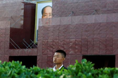 A security officer keeps watch near the portrait of the late Chinese chairman Mao Zedong in Tiananmen Square in Beijing, China May 19, 2019. REUTERS/Thomas Peter