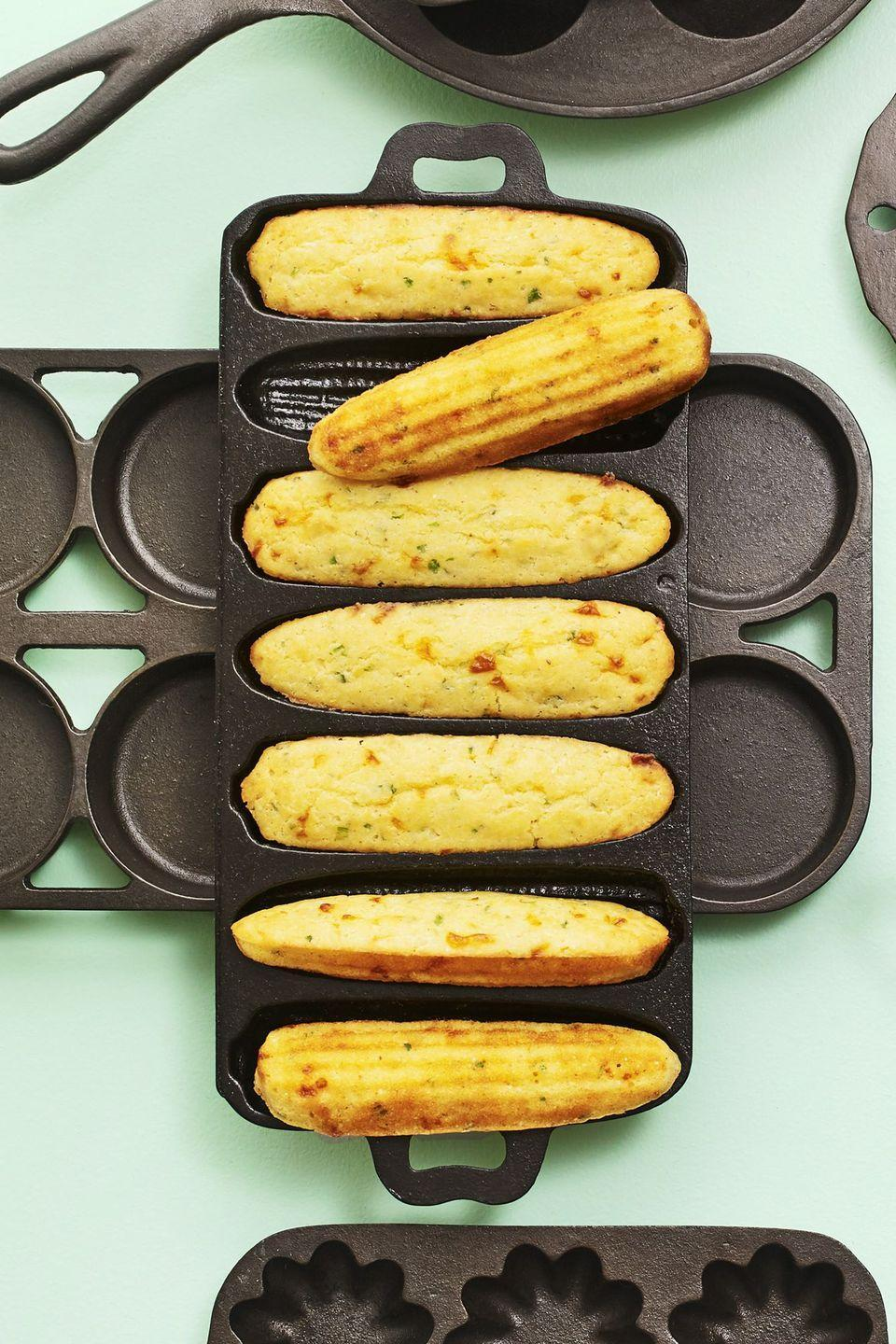 "<p>While you don't have to bake this cheesy cornbread in a cast iron pan, it's even more tasty if you do. And here's an even better idea: For a fun look, cook 'em in <a href=""https://www.amazon.com/Bayou-Classic-7490-Cast-Cornbread/dp/B000BTYL14/?tag=syn-yahoo-20&ascsubtag=%5Bartid%7C10050.g.896%5Bsrc%7Cyahoo-us"" rel=""nofollow noopener"" target=""_blank"" data-ylk=""slk:corn-shaped cast iron molds"" class=""link rapid-noclick-resp"">corn-shaped cast iron molds</a>.<br></p><p><strong><a href=""https://www.countryliving.com/food-drinks/a19705455/scallion-cornbread-recipe/"" rel=""nofollow noopener"" target=""_blank"" data-ylk=""slk:Get the recipe"" class=""link rapid-noclick-resp"">Get the recipe</a>.</strong></p><p><strong><a class=""link rapid-noclick-resp"" href=""https://www.lodgecastiron.com/product/seasoned-cast-iron-cornstick-pan"" rel=""nofollow noopener"" target=""_blank"" data-ylk=""slk:SHOP CORN STICK PANS"">SHOP CORN STICK PANS</a><br></strong></p>"
