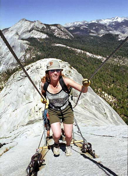 FILE - In this June 6, 2004 file photo, Thea Roberts, of Oakland, Calif., pulls herself up the cable route on the way to the summit of Half Dome, in Yosemite National Park. A long-awaited plan that officials say will make safer the iconic climb up Half Dome in Yosemite National Park has been approved. The hand-rail cables that some environmental groups argued don't belong in a wilderness will stay, as will a lottery that will limit the number of hikers to roughly 400 a day. Over the past decade the route has been inundated with up to 1,200 nature lovers, causing traffic jams and a surge in calls for rescue. (AP Photo/Robert F. Bukaty)