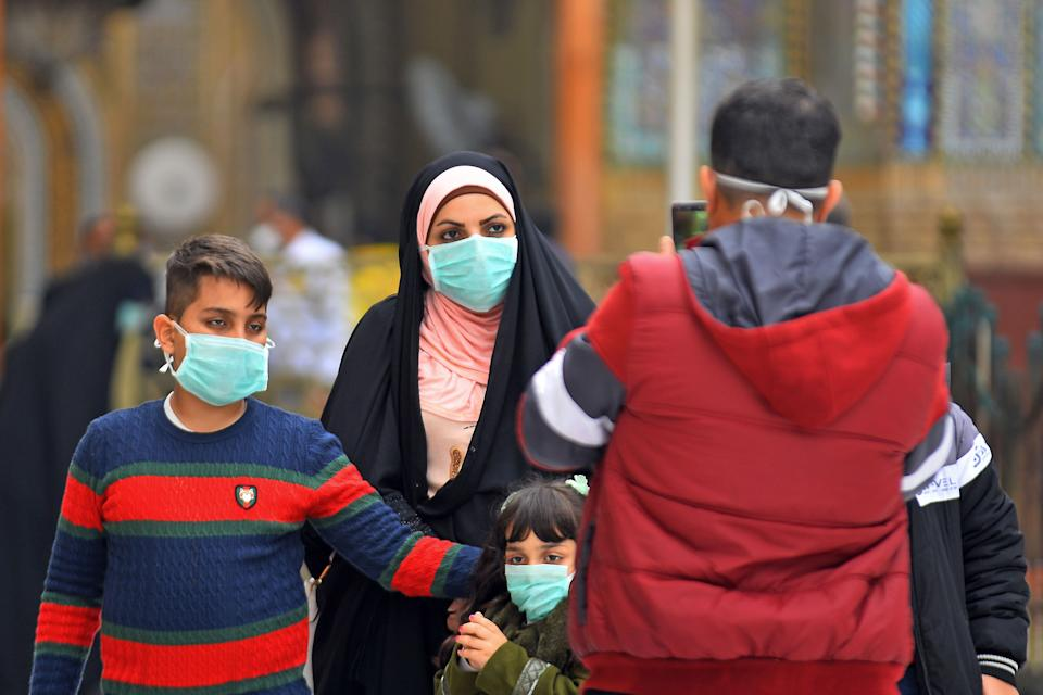 Iraqis wearing masks walk on February 25, 2020 in the partially deserted streets of Iraq's central shrine city of Najaf, where the first case of coronavirus COVID-19 has been documented in Iraq. - Iraq on February 24 confirmed its first novel coronavirus case in an elderly Iranian national in Najaf, according to health officials. A country with a dilapidated healthcare system, Iraq often hosts pilgrims and religious students from Iran, where at least a dozen people have died of the novel coronavirus since an outbreak there was first reported last week. Iraq had blocked travel to and from the Islamic republic days before announcing a seminary student in Najaf was the country's first confirmed case. (Photo by Haidar HAMDANI / AFP) (Photo by HAIDAR HAMDANI/AFP via Getty Images)