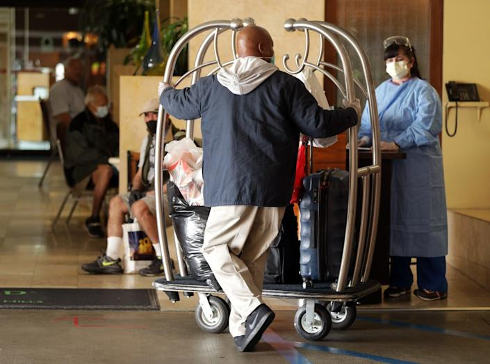 Omar Spry pushes a cart of bags into a West L.A. hotel that has been turned into housing for homeless people during the coronavirus pandemic.