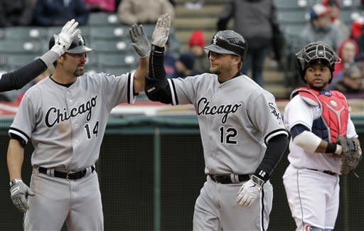 With Cleveland Indians catcher Carlos Santana watching at right, Chicago White Sox's A.J. Pierzynski (12) is congratulated by teammate Paul Konerko (14) after hitting a three-run home run in the sixth inning of a baseball game in Cleveland on Wednesday, April 11, 2012. (AP Photo/Amy Sancetta)