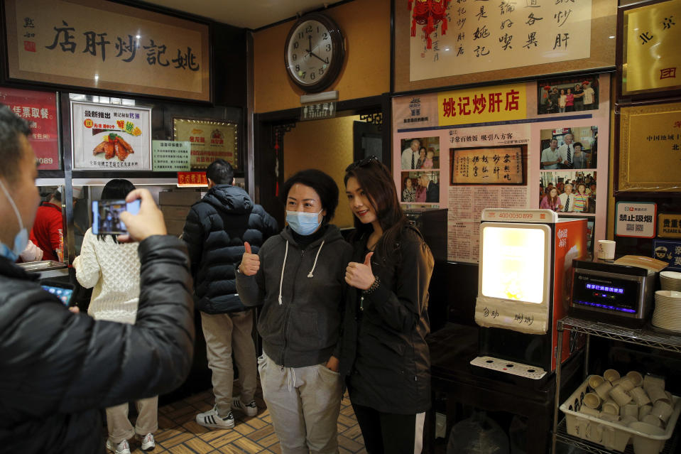 Customers pose for a souvenir photo with Joe Biden's photos on display in the background at a restaurant where he visited in 2011 as U.S. vice president, in Beijing, Sunday, Nov. 8, 2020. World leaders congratulated U.S. President-elect Biden on his victory, cheering it as an opportunity to fortify global democracy and celebrating the significance of Americans having their first female vice president. (AP Photo/Andy Wong)