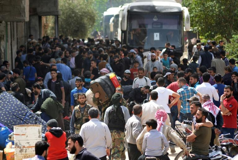 Rebels and civilians prepare to be evacuated from the southern outskirts of Damascus for opposition-held parts of northern Syria on May 3, 2018 under a negotiated withdrawal to secure the last opposition holdouts of the capital