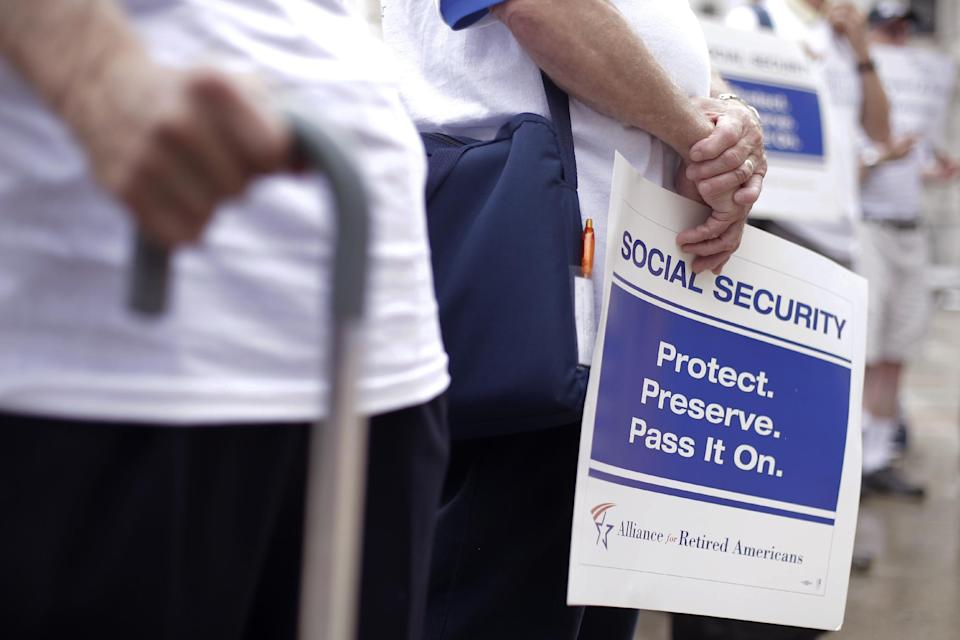 """Demonstrators form a symbolic chain to protest agents a proposed change in the formula for determining annual Social Security benefits known as """"chained CPI,"""" Tuesday, July 2, 2013, in Philadelphia. Social Security has continuously been under fire due to it being underfunded, but research shows it as an effective anti-poverty measure. (AP Photo/Matt Rourke)"""