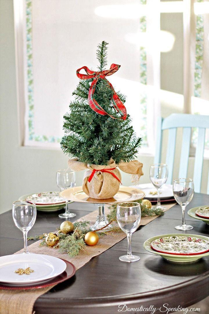 "<p>Go all out for a holiday table centerpiece, and place a miniature evergreen—topped with a ribbon—in the middle of your spread.</p><p>See more at <a href=""http://www.domestically-speaking.com/2013/12/christmas-home-tour-2013.html"" rel=""nofollow noopener"" target=""_blank"" data-ylk=""slk:Domestically Speaking"" class=""link rapid-noclick-resp"">Domestically Speaking</a>. </p>"