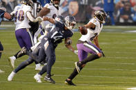 Baltimore Ravens cornerback Marcus Peters (24) is chased by Tennessee Titans wide receiver Kalif Raymond (14) after Peters intercepted a pass late in the fourth quarter to seal the Ravens' win in an NFL wild-card playoff football game Sunday, Jan. 10, 2021, in Nashville, Tenn. The Ravens won 20-13. (AP Photo/Mark Zaleski)