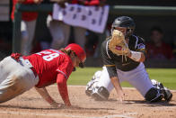 Philadelphia Phillies' Alec Bohm (28) slides safely past a tag-attempt by Pittsburgh Pirates catcher Jacob Stallings to score during the fifth inning of a spring training exhibition baseball game in Bradenton, Fla., Sunday, March 14, 2021. Bohm scored on a single by Matt Joyce. (AP Photo/Gene J. Puskar)