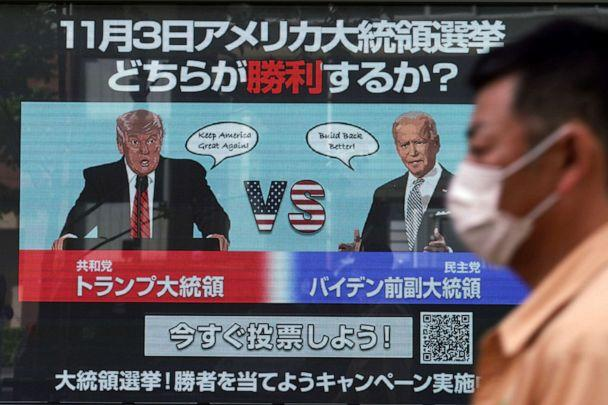 PHOTO: A man walks past a screen showing Republican President Donald Trump, left, and Democratic candidate and former Vice President Joe Biden for an online voting to predict the winner in the U.S. presidential election, in Tokyo, Oct. 26, 2020. (Eugene Hoshiko/AP)