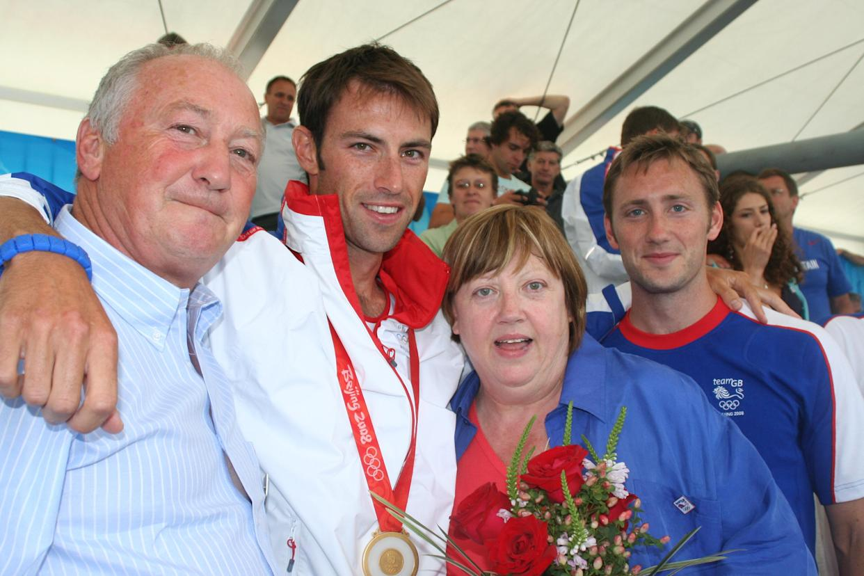 Mark celebrates 2008 Olympic gold in Beijing with his mum and dad and brother Ross