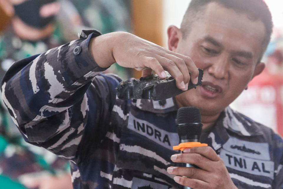 A Indonesian Navy personnel shows a piece of debris believed to be from the sunken submarine.