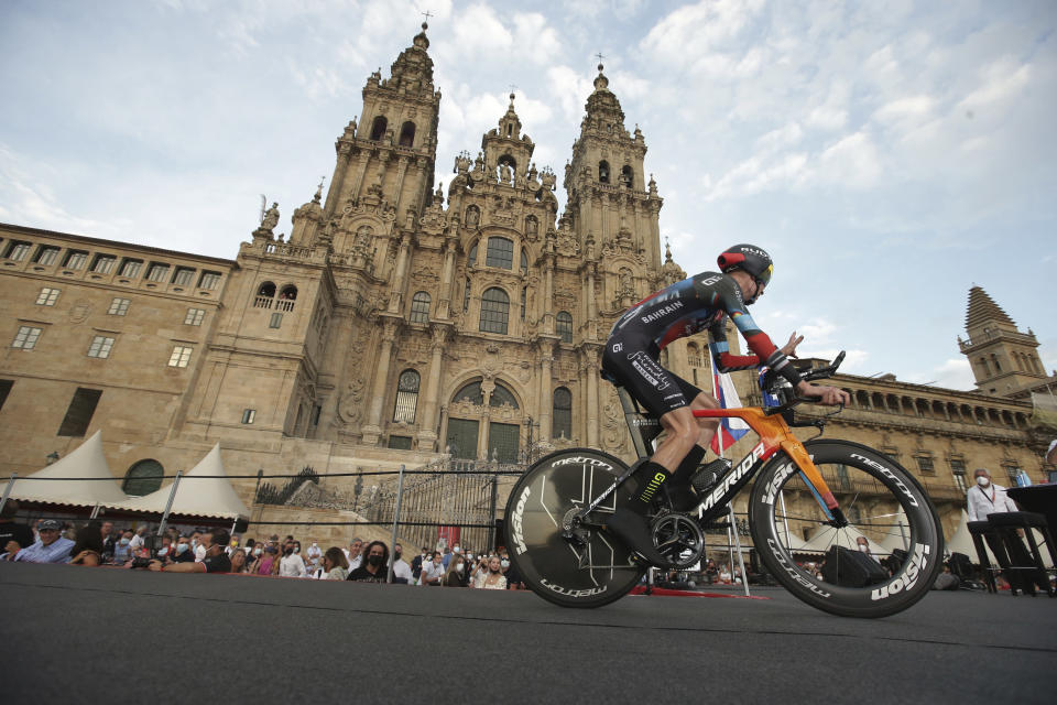 Jack Haig of Australia rides past the cathedral during a time trial on the 21st and last stage of the Vuelta Cycling race in Santiago, Spain, Sunday, Sept. 5, 2021. (AP Photo/Luis Vieira)