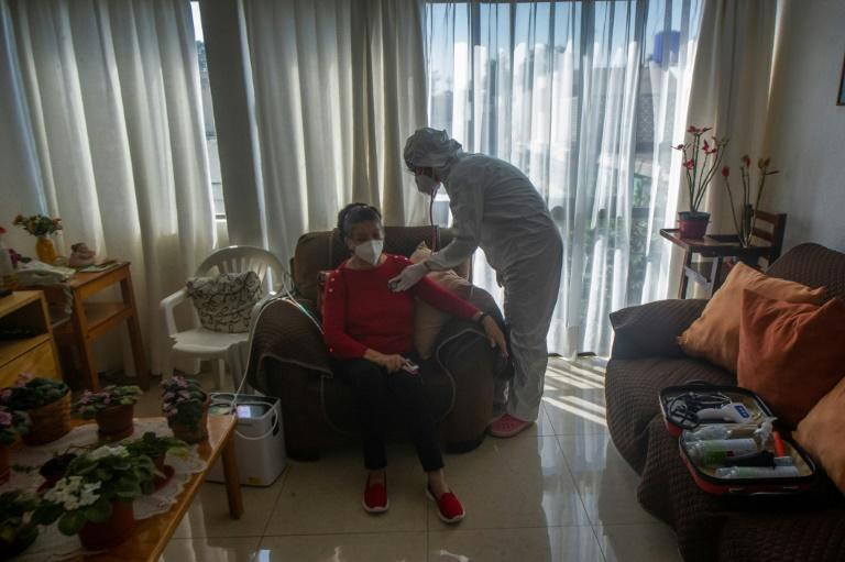 Karla Montano, one of Mexico's many community-based doctors, wears a protective suit to visit a coronavirus patient at home in the capital