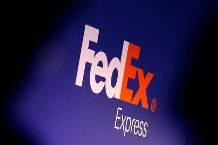 FILE PHOTO: People stand near the FedEx Express logo during the presentation of the future extension of the FedEx hub in Roissy-en-France