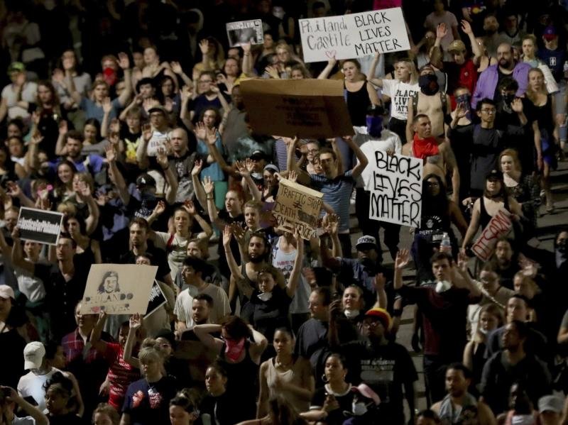 Demonstrators march and hold signs along Interstate 94 after a Minnesota police officer was cleared in the fatal shooting of Philando Castile: AP