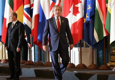 U.S. President George W. Bush (R) walks past Russian President Vladimir Putin as G8 leaders and outreach leaders gather for a group photo at the G8 summit in St. Petersburg, Russia, in this July 17, 2006 file photo. REUTERS/Jason Reed/Files