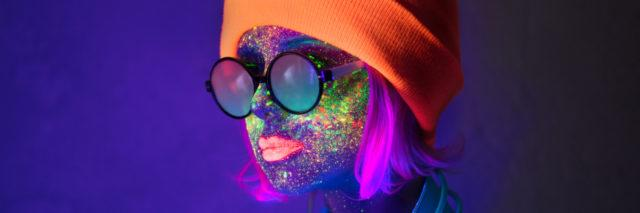 Woman in hat with fluorescent paint on lips and face and headphones.