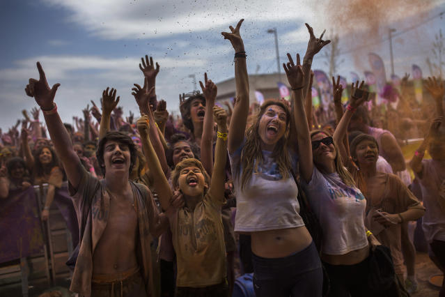 <p>Revelers, covered in colored powder celebrate at a Holi Run festival in Madrid, April 12, 2015. (AP Photo/Andres Kudacki) </p>