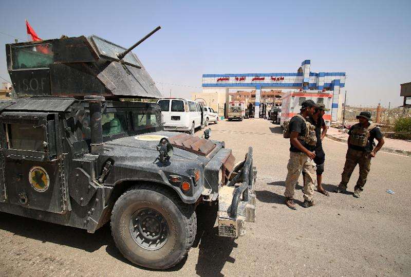 Members of the Iraqi counter-terrorism forces stand next to an armed vehicle on June 23, 2016