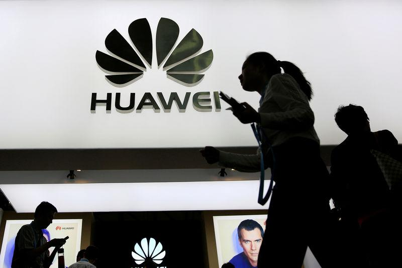 FILE PHOTO: People walk past a sign board of Huawei at CES (Consumer Electronics Show) Asia 2016 in Shanghai, China May 12, 2016. REUTERS/Aly Song/File Photo