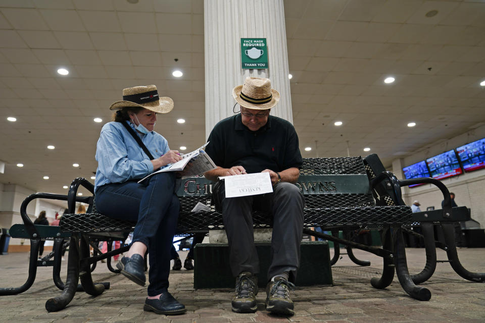 A couple looks over a racing program before the 147th running of the Kentucky Derby at Churchill Downs, Saturday, May 1, 2021, in Louisville, Ky. (AP Photo/Brynn Anderson)