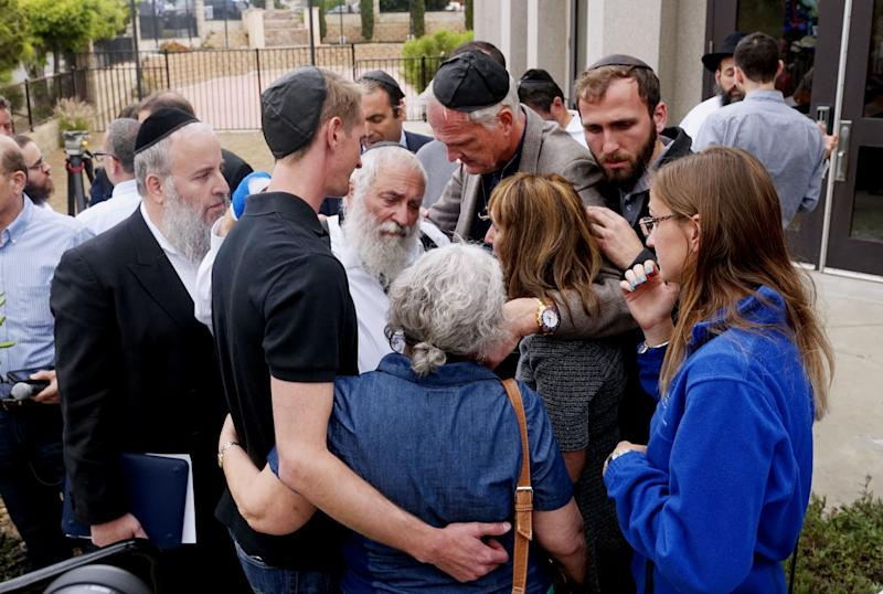 Rabbi Yisroel Goldstein (center) hugs his congregants after a press conference outside the Chabad of Poway Synagogue on April 28, 2019. The rabbi was wounded in a shooting at his California synagogue the previous day. (Photo: SANDY HUFFAKER via Getty Images)