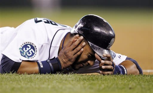 Seattle Mariners' Franklin Gutierrez lies on the ground after being hit on the jaw by the ball in a pickoff-attempt at first base by Boston Red Sox pitcher Franklin Morales in the fourth inning of a baseball game on Thursday, June 28, 2012, in Seattle. Gutierrez left the game. (AP Photo/Elaine Thompson)