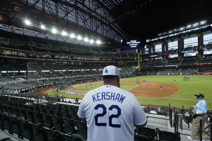 A Los Angeles Dodgers fan watches during batting practice before Game 6 of the baseball World Series between the Los Angeles Dodgers and the Tampa Bay Rays Tuesday, Oct. 27, 2020, in Arlington, Texas.(AP Photo/Eric Gay)