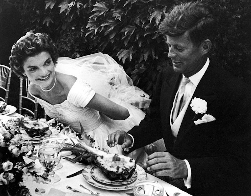 Senator John Kennedy and bride Jacqueline sitting together outdoors at table, eating pineapple salad, at their wedding reception. (Photo by Lisa Larsen/Time & Life Pictures/Getty Images)
