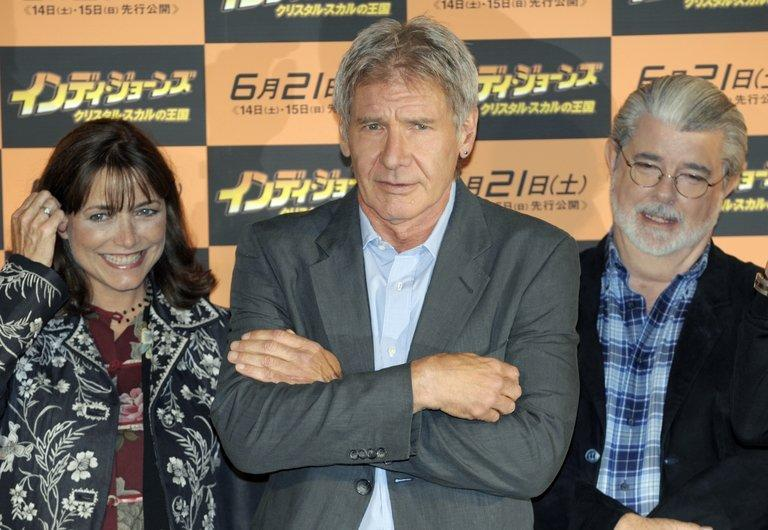 Actor Harrison Ford (C), actress Karen Allen and film producer George Lucas pose in Tokyo