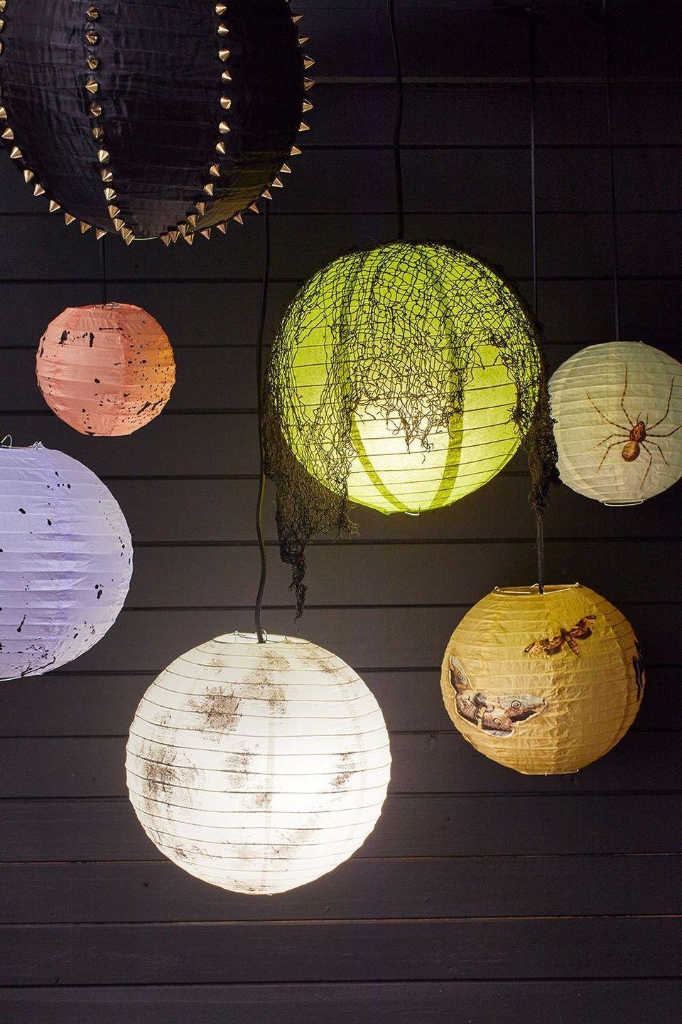 """<p>Upgrade basic paper lanterns with paint, gauze, studs and clip art from an eerie look. </p><p><a href=""""https://www.goodhousekeeping.com/home/craft-ideas/a34329004/diy-halloween-lantern-tutorial/"""" rel=""""nofollow noopener"""" target=""""_blank"""" data-ylk=""""slk:Get the tutorial >>"""" class=""""link rapid-noclick-resp""""><em>Get the tutorial >></em></a></p>"""