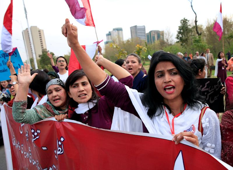 Demonstrators hold banners and shout slogans during a rally.