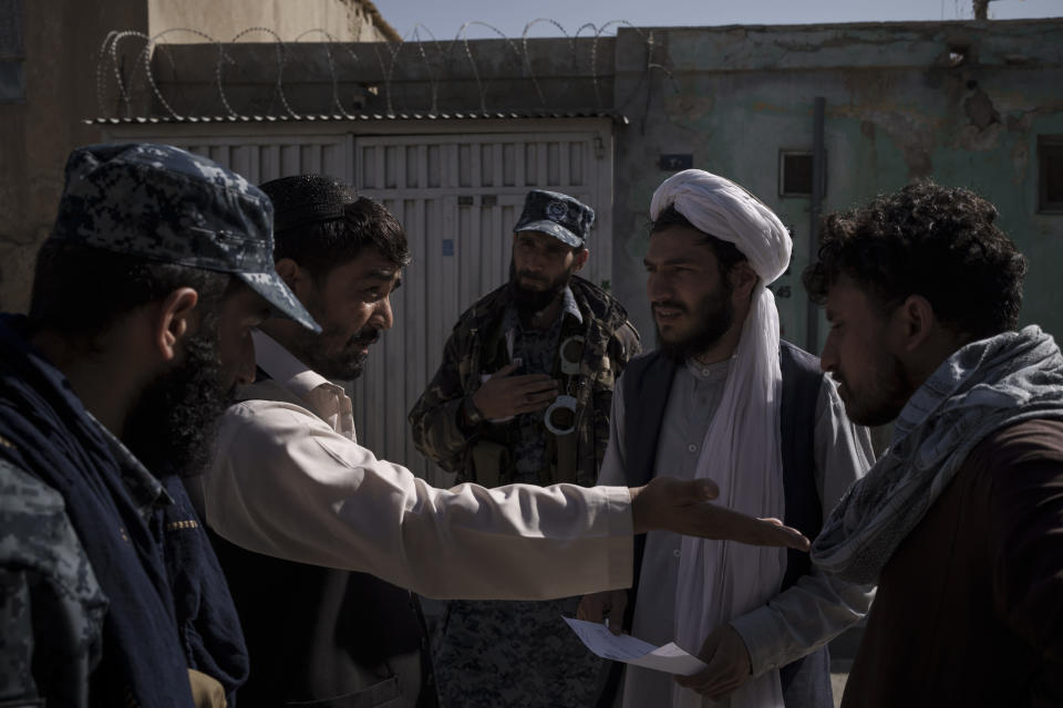 Taliban fighter listen as two men argue over a claim of late rent payment in Kabul, Afghanistan, Wednesday, Sept. 15, 2021. It is a symbol of the moment of transition they find themselves in: Once warriors embedded in Afghanistan's rugged mountains, now the Taliban are an urban police force. (AP Photo/Felipe Dana)